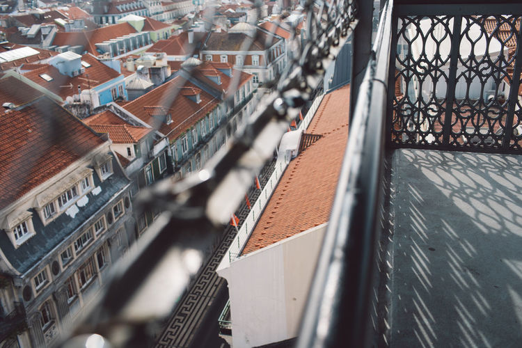 High angle view of buildings in city seen through fence