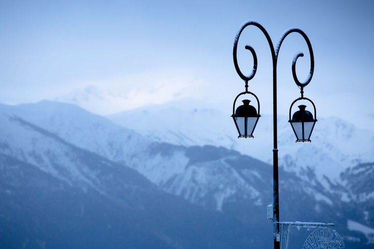 Street light and snowcapped mountains against sky
