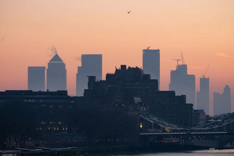 Modern buildings in city against sky during sunrise