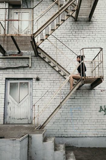 Fashion Sitting Woman Architecture Building Building Exterior Built Structure Connection Day Full Length Industry Lifestyles Metal Model Old One Person Outdoors Railing Real People Staircase Steps And Staircases Urban Urbanphotography Wall - Building Feature #urbanana: The Urban Playground Summer In The City