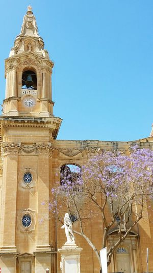 Blue Clear Sky Architecture Tower Church Church Towers No People Clock Tower Outdoors Naxxar Malta Architecture Malta Maltaphotography Purple Flowers Limestone