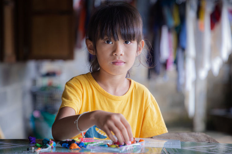 Portrait of cute girl playing with clay at home