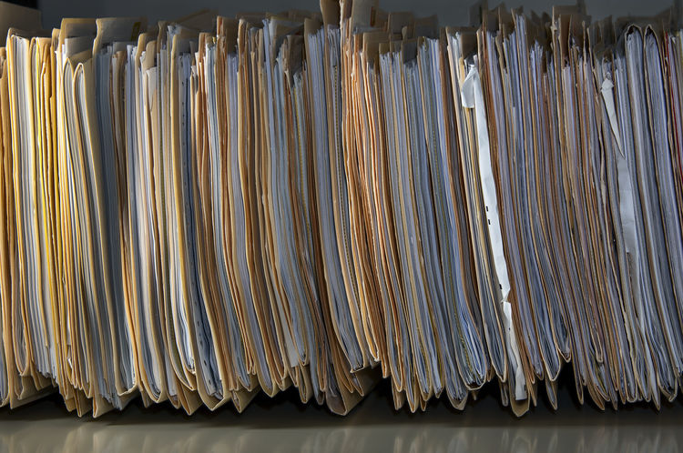 Crammed file folders packed tightly on shelf. File Filing Papers Forms Productivity Archives Bureaucracy Clerical Crammed Document Filing Filing Cabinet Manilla Folder No People Office Supply Office Work Overwork Paper Paperwork Records Stack