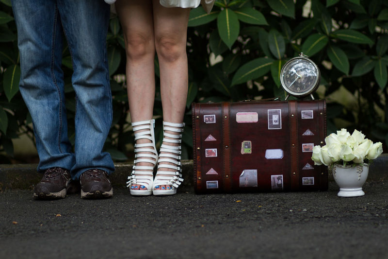Low section of couple standing by luggage on road