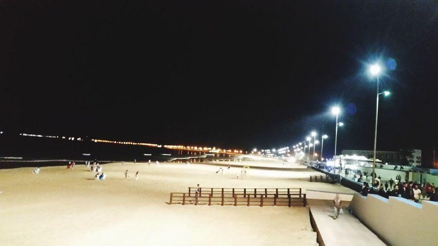 Illuminated street lights against sky at night