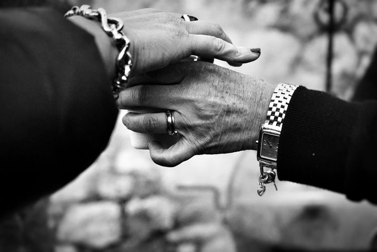 Midsection of couple holding hands against blurred background