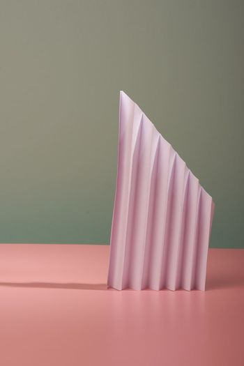 Close-up of pink paper on table against wall