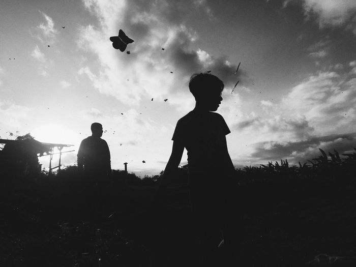 Silhouette people standing on field against sky
