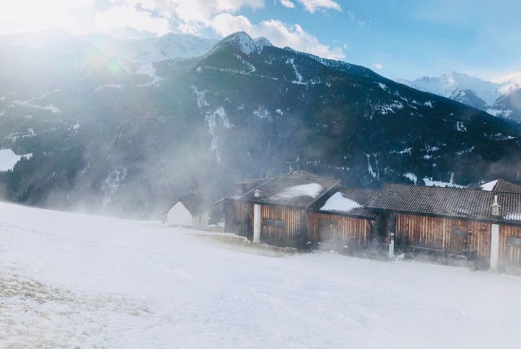 Snow covered houses by mountain against sky