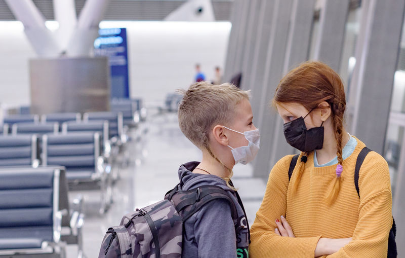 Siblings wearing mask looking at each other while standing at airport