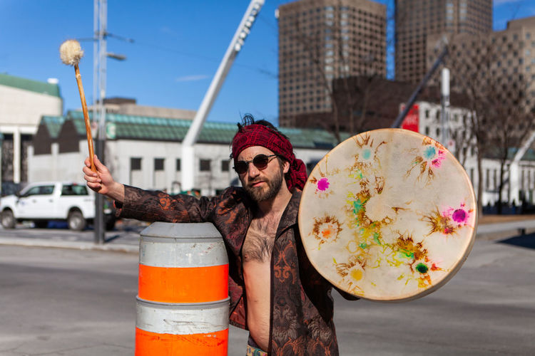 Portrait of man holding drum while standing at city