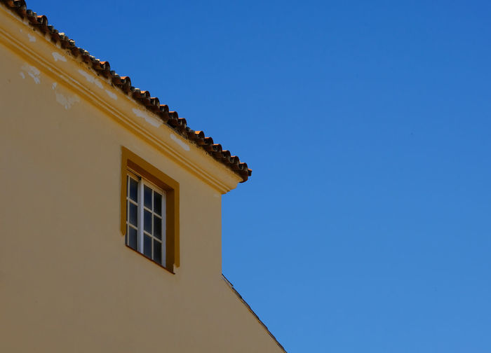 Architectural Detail Blue Building Exterior Clear Blue Sky Clear Sky Complementary Colors Copy Space Copy Space In Sky Flaking Paint High Contrast High Resolution House Lines Low Angle View Minimalism No People Roof Slanted Spain, Andalucia, Malaga Torremolinos Window Yellow Yellow House  Paint The Town Yellow