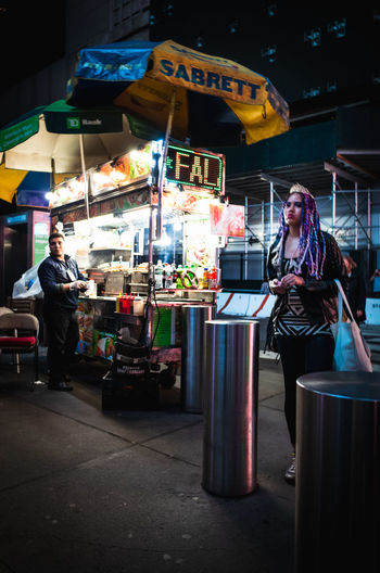 People at market stall at night