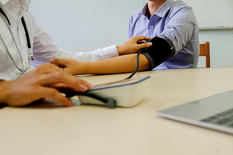 Surface level of doctor examining blood pressure of patient