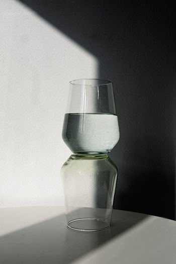 Close-up of water in glass on table against wall