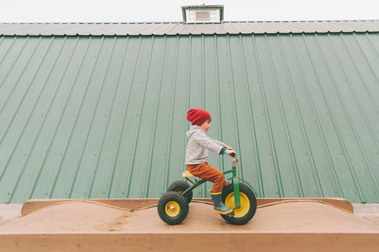 Rear view of boy riding motorcycle on bicycle
