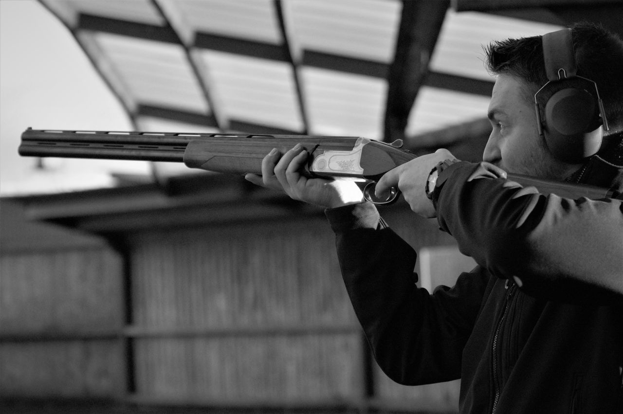gun, weapon, aiming, rifle, shooting a weapon, holding, real people, protection, leisure activity, one person, standing, men, handgun, lifestyles, protective workwear, indoors, close-up, day, camouflage clothing, young adult, human hand, people, adult