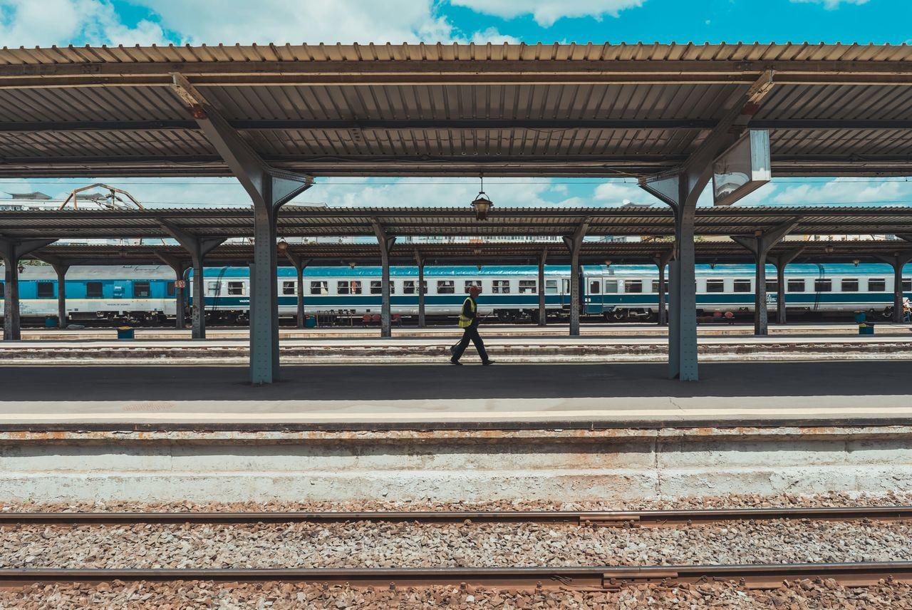 Side view of man walking on railroad station platform