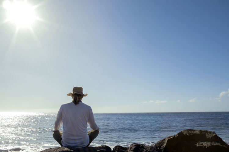 Rear view of man against sea against sky