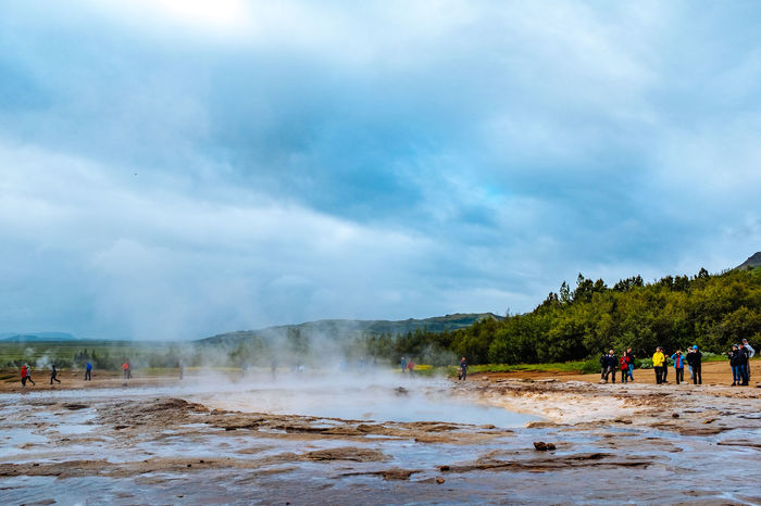 Iceland Beauty In Nature Cloud - Sky Day Erupting Geology Geyser Heat - Temperature Hot Spring Leisure Activity Lifestyles Men Nature Outdoors Physical Geography Real People Scenics Sky Smoke - Physical Structure Steam Tourism Travel Travel Destinations Vacations Volcanic Landscape Water