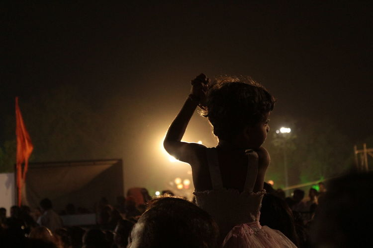 Rear view of girl with crowd enjoying music concert at night