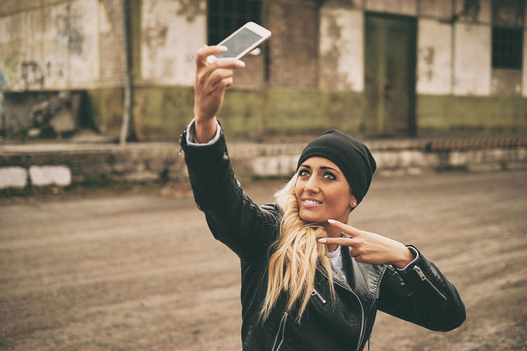 Fashionable young woman wearing leather jacket taking selfie with smart phone
