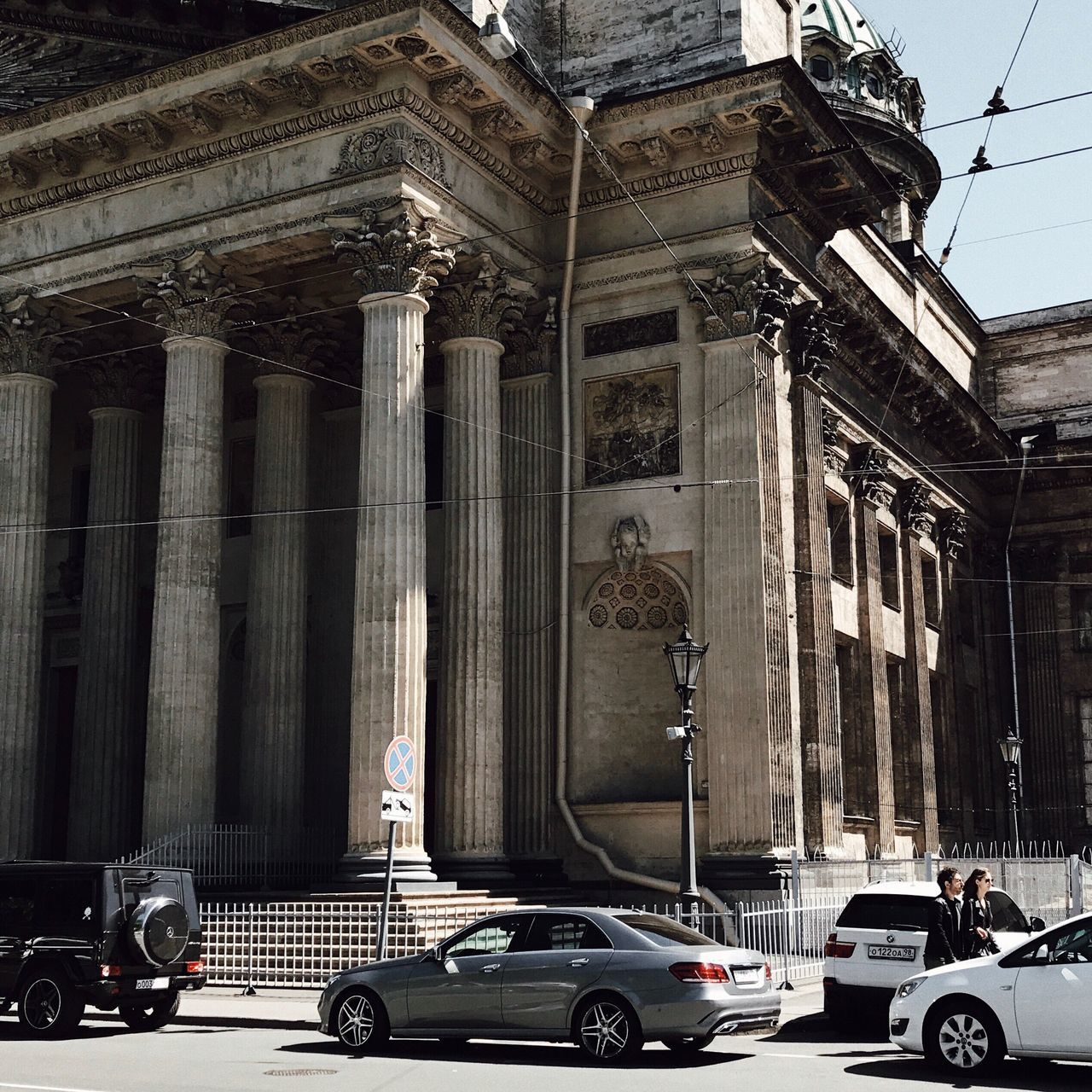 architecture, architectural column, building exterior, built structure, car, transportation, day, land vehicle, outdoors, statue, travel destinations, no people