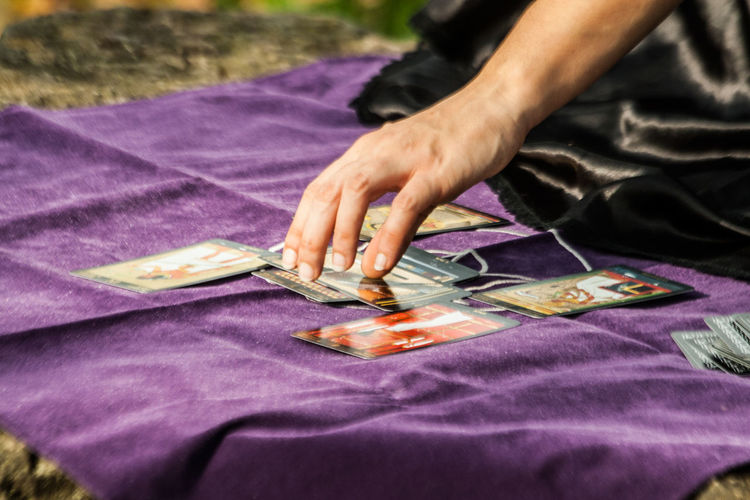 Cropped image of fortune teller with tarot cards
