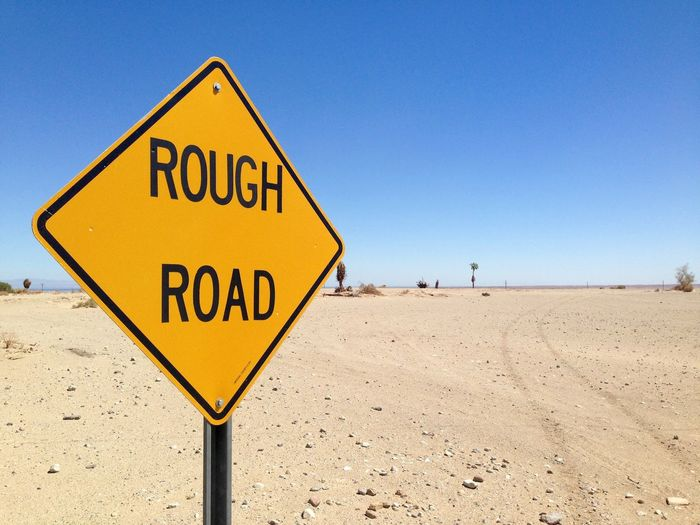 Road sign on barren landscape against clear blue sky