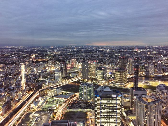 High Angle View Of Illuminated Cityscape Against Cloudy Sky At Dusk