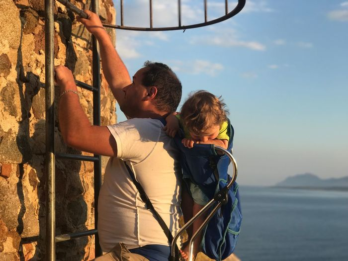 Side view of father climbing ladder on wall while carrying son against sky