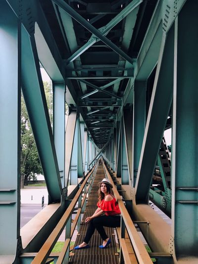 Portrait Of Woman Sitting On Railing Under Bridge