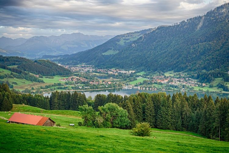 Scenic view of immenstadt by lake in valley against cloudy sky