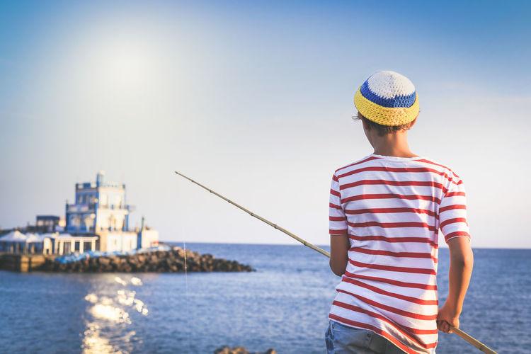 Rear view of boy fishing in sea
