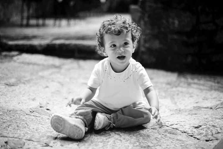 Cute baby girl looking away while sitting on street
