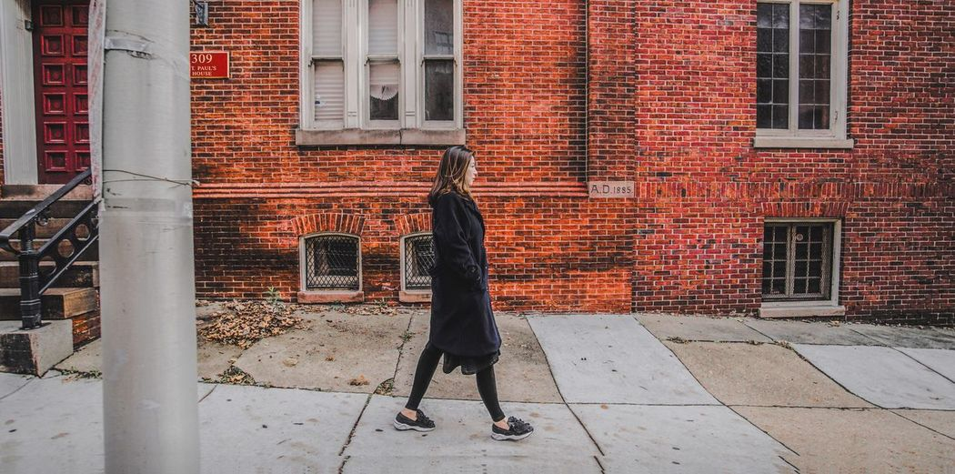 Rear view of man walking on brick wall
