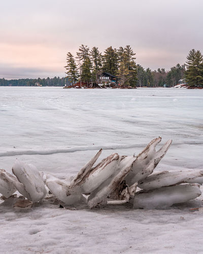 Scenic view of private island on frozen lake against sunrise during winter