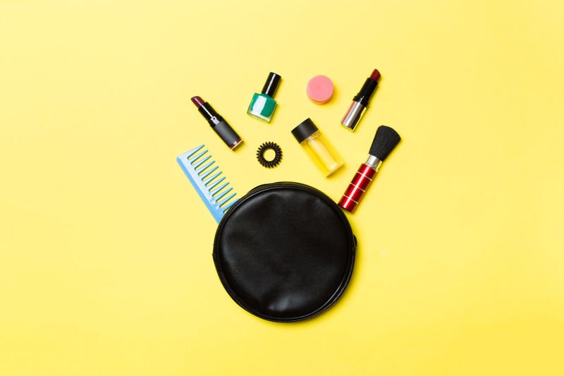 Directly above shot of purse with beauty products over yellow background
