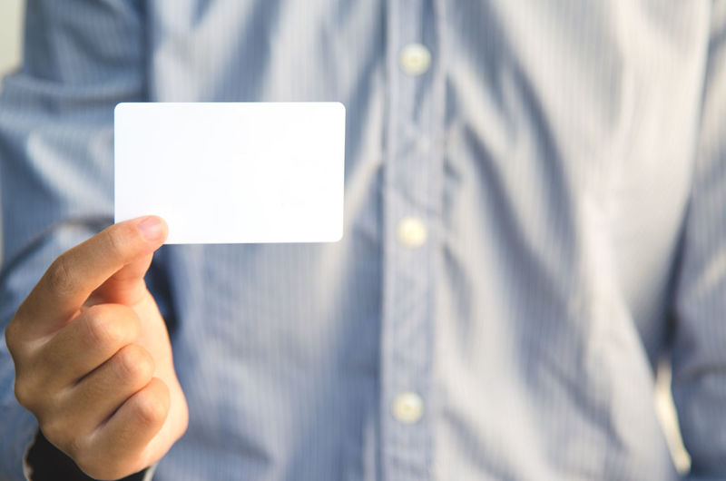 Midsection Of Man Holding Blank Business Card Against White Background