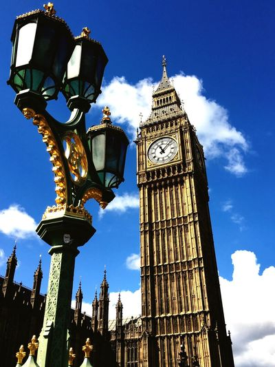 Low angle view of street light and big ben against sky