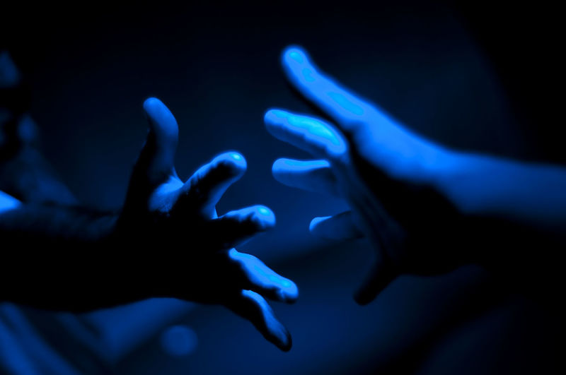Cropped hands of people in illuminated room