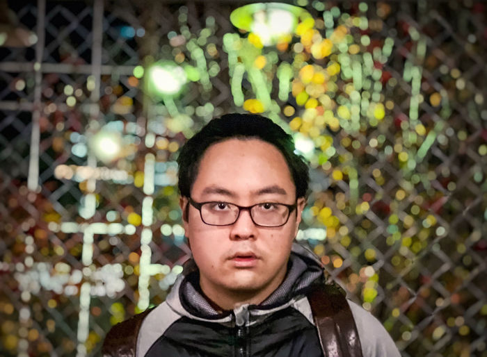 Portrait of a man wearing eyeglasses against metal fence, street and neon lights.