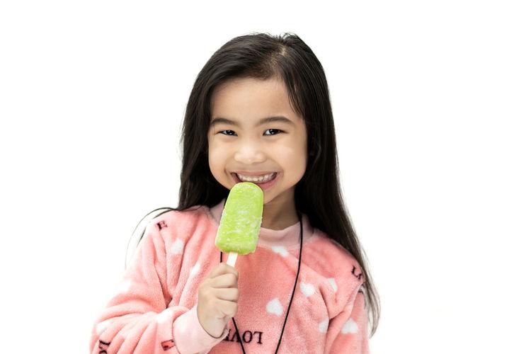 Portrait of smiling girl holding ice cream against white background