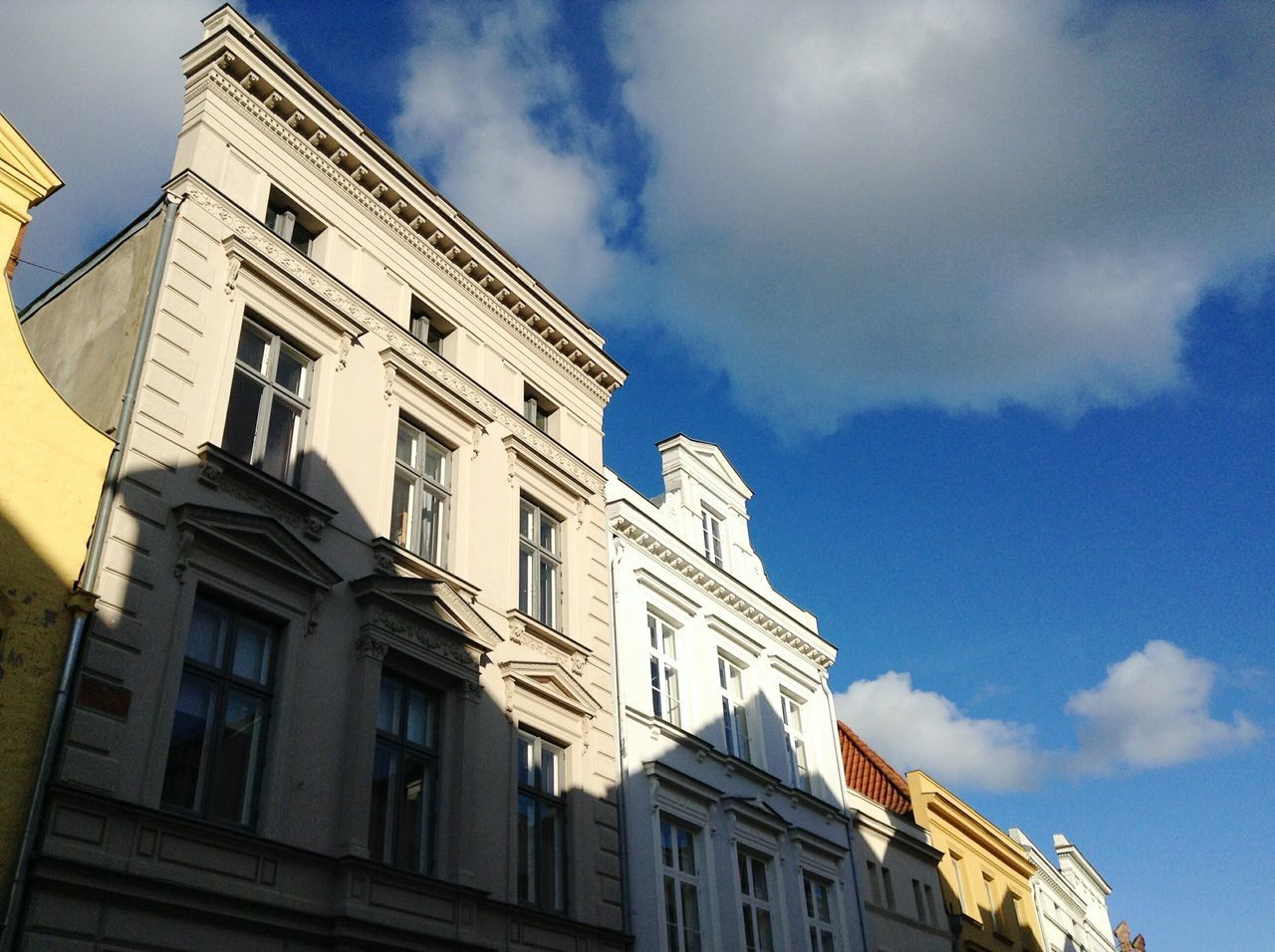 architecture, low angle view, building exterior, sky, built structure, cloud - sky, window, day, no people, outdoors, city