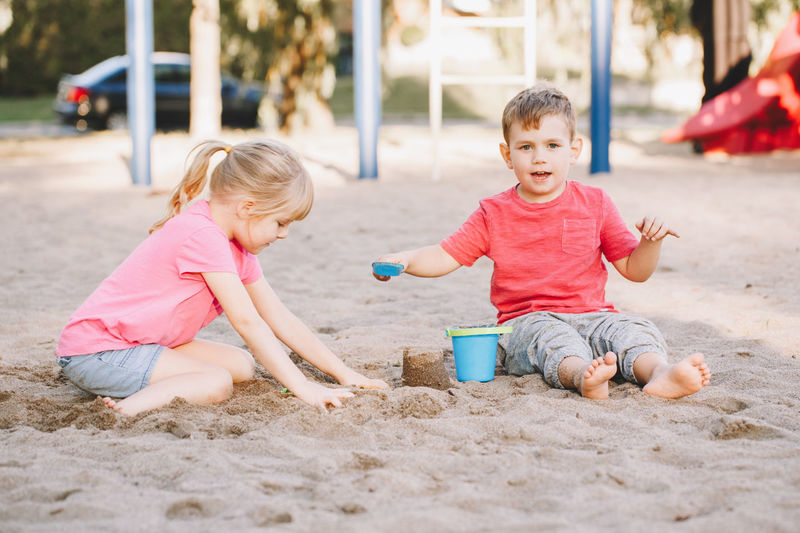 Siblings playing on sand