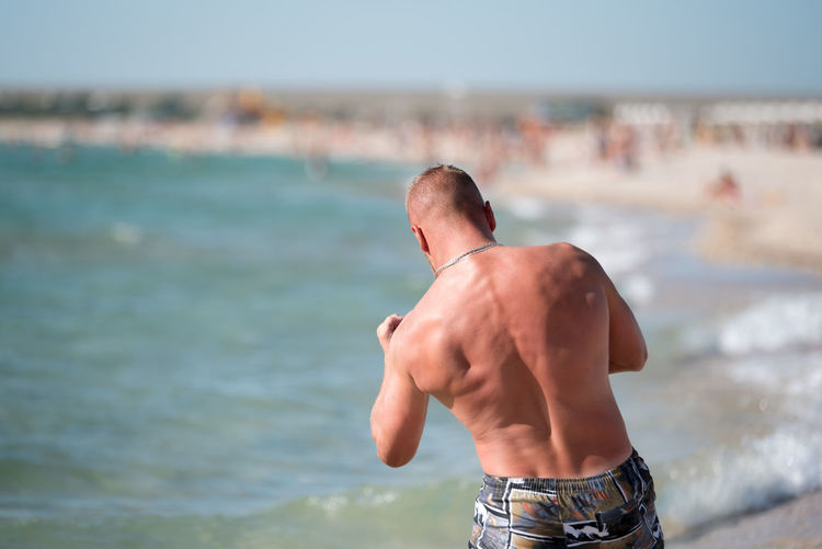 Rear view of shirtless man boxing at beach against sky