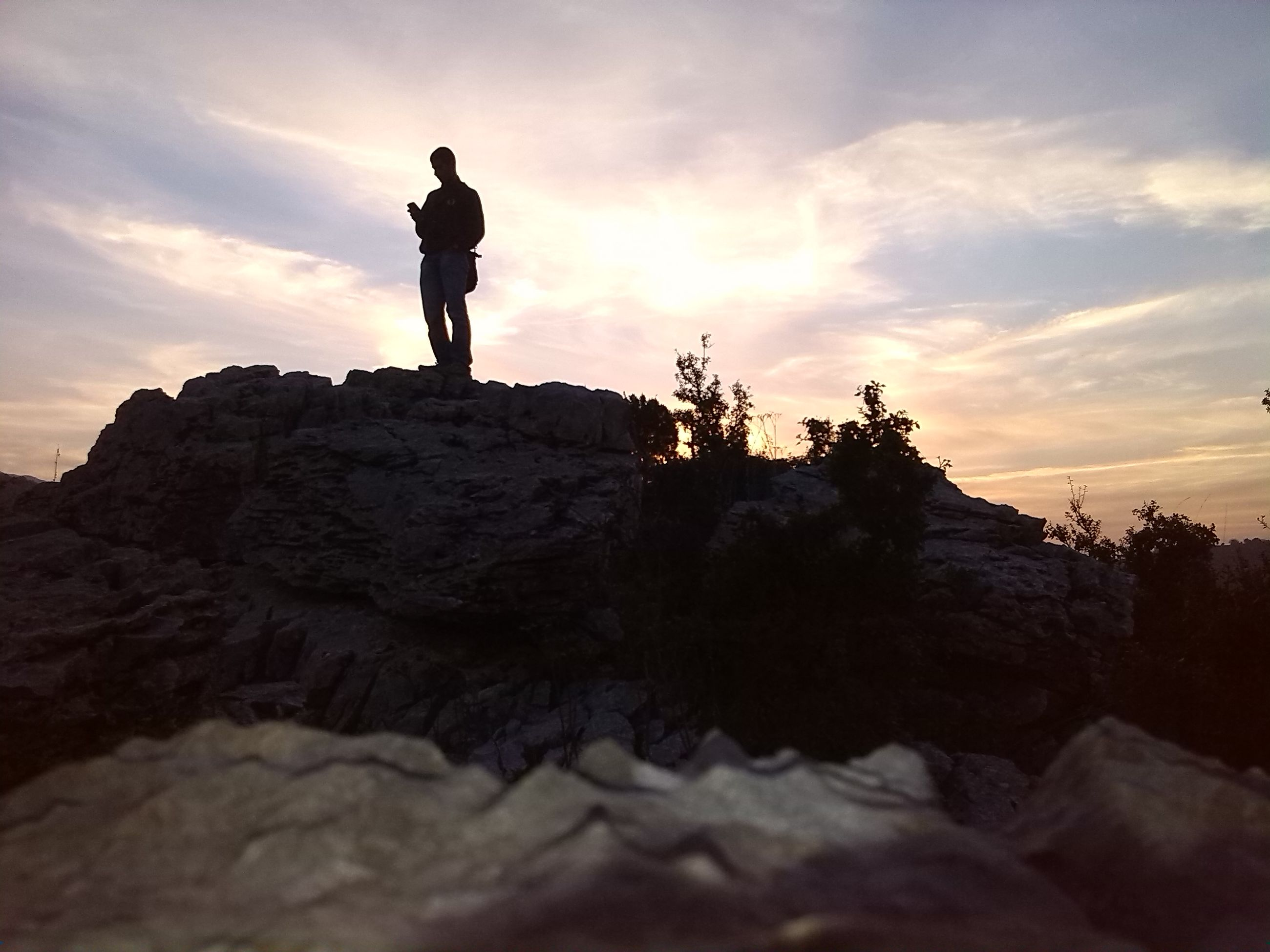 sky, silhouette, lifestyles, rock - object, leisure activity, standing, full length, cloud - sky, sunset, low angle view, men, tranquil scene, rock formation, tranquility, nature, scenics, cloud, beauty in nature