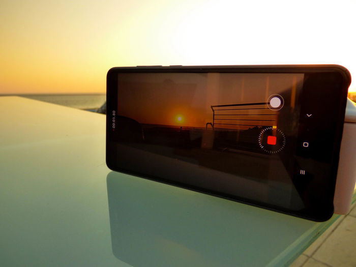 Close-up of camera with reflection on mirror against orange sky