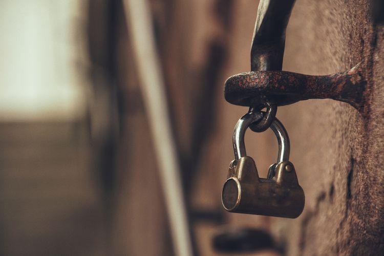 Close-up of padlock hanging on metallic latch