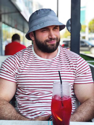 Caucasian Drink One Person Facial Hair Front View Hat Beard Casual Clothing Sitting Men Refreshment Real People Food And Drink Drinking Leisure Activity Young Men Glass Waist Up Lifestyles Outdoors Cocktail